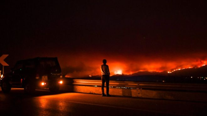 A man stands on the roadside watching a wildfire at Anciao, Leiria, central Portugal, on June 18, 2017