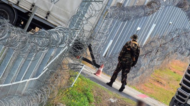 A Hungarian soldier patrols at the border fence at the Tompa border station transit zone - expanded to become one of two new detention centres for asylum seekers - on 6 April 2017
