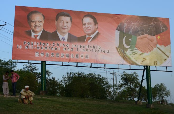 A Pakistani man sits under a welcoming billboard ahead of a visit by Chinese President Xi Jinping in Islamabad on April 17, 2015.
