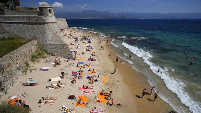 tourists enjoy a day out at the Citadel Beach in central Ajaccio on the French Mediterranean island of Corsica