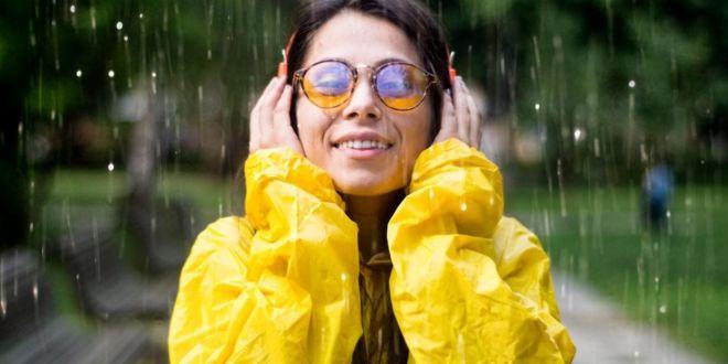 زنی با بارانی زرد زیر باران