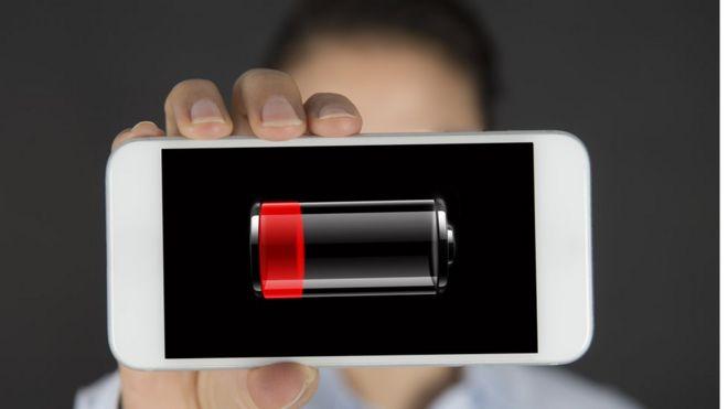 Celular con batería casi agotado en manos de mujer