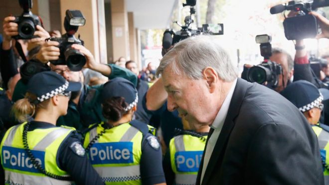 George Pell enters Melbourne Magistrates' Court, shielded from the media by a line of police