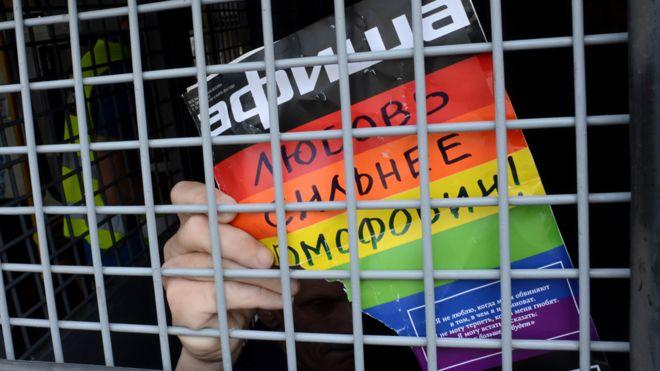 """Un activista gay detenido en Moscú con un aviso que lee """"el amor es más fuerte que la homofobia""""."""