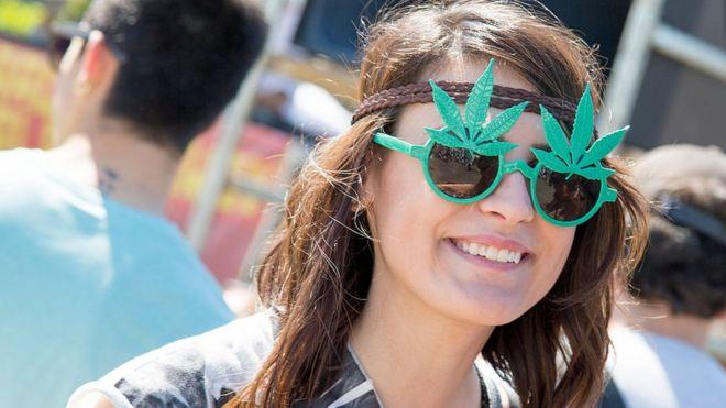 Mulher usando óculos com folha de maconha