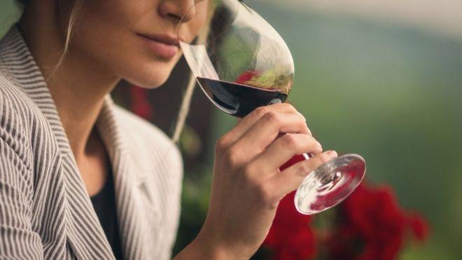 Mulher bebe taça de vinho tinto