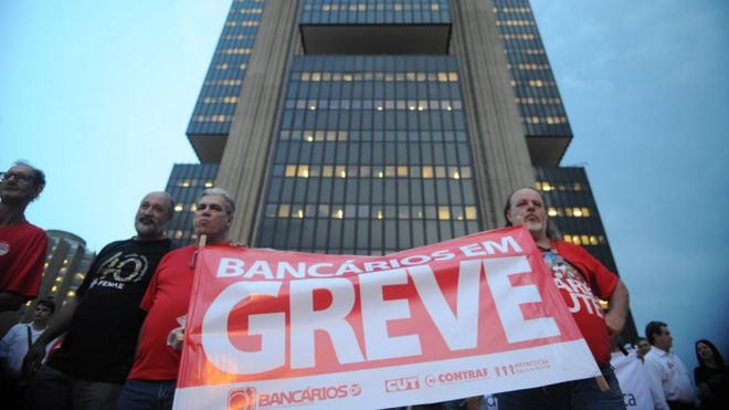 Bancários erguem cartaz de greve em frente a sede do Banco Central, em Brasília, em 2014