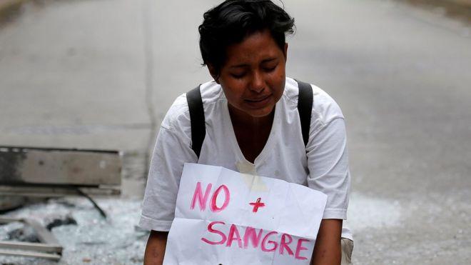 """Una joven con un cartel que dice """"No más sangre"""""""