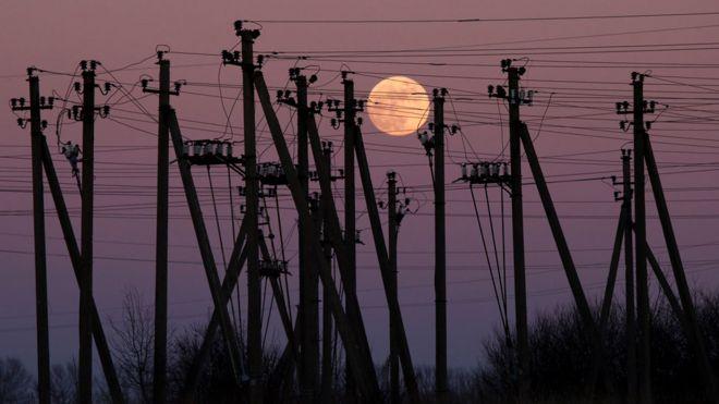 Luna llena entre torres de electricidad en Virbalis, Lituania