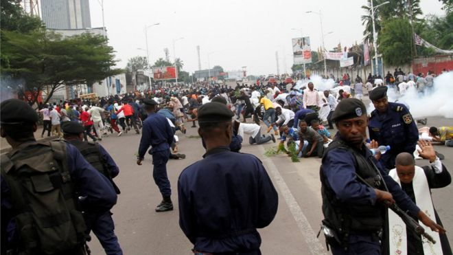 Riot policemen fire teargas canisters to disperse demonstrators during a protest - many people, including a priest, can be seen kneeling, hands raised