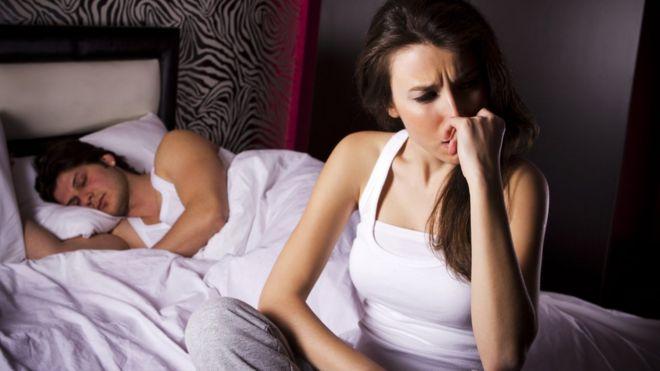 Mujer infeliz en cama hombre dormido