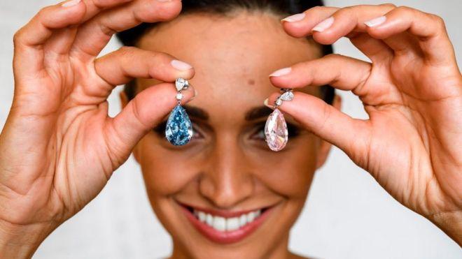 Una modelo muestra dos diamantes valorados en millones de dólares.