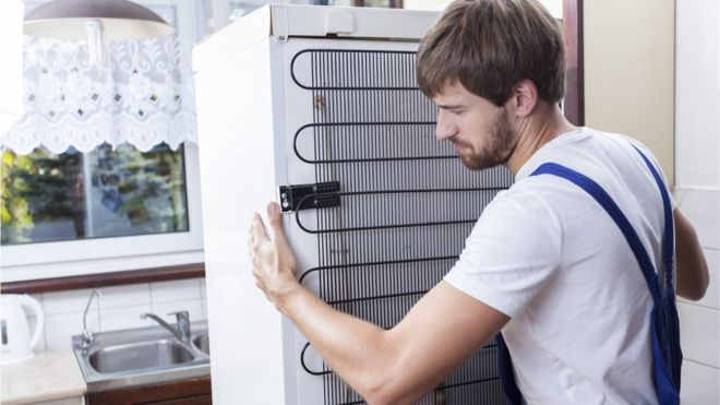 workman removes fridge
