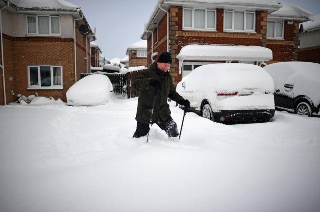 A man makes his way through snow in a housing estate