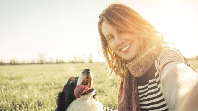 فتاة تنظر مبتسمة إلى الكاميرا وهي تلتقط صورة سيلفي مع كلبها