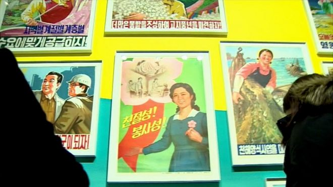 Visitors are staring at North Korean posters. On the centre poster with fluorescent green coloured background, a young woman is emphasising the importance of kindness and servitude.