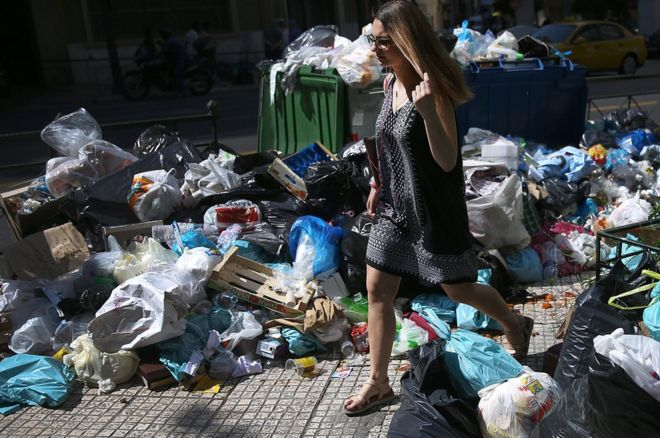 A woman walks through rubbish in Athens