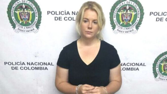 Cassie Sainsbury stands in front of a police banner soon after her arrest