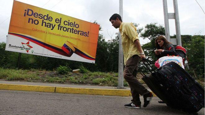 Dos venezolanos cruzan la frontera entre Colombia y Venezuela.