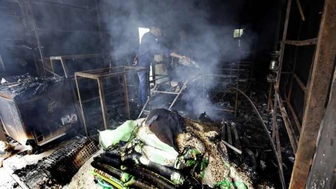 A Sri Lankan Muslim tries to put out the remaining embers in his fire-gutted business in Digana town, Kandy in Sri Lanka, 7 March 2018