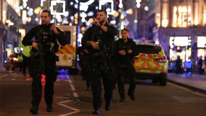 Armed police patrol along Oxford Street