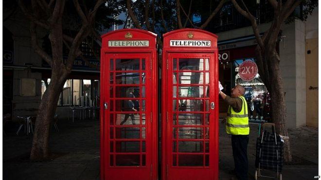 Un hombre limpia una caseta telefónica en la calle en Gibraltar.