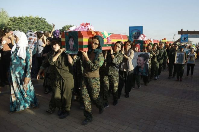Syrian Kurd women fighters carry the coffin of a comrade killed in Manbij  at a funeral