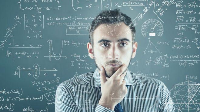 Un hombre frente a un tablero con problemas para resolver