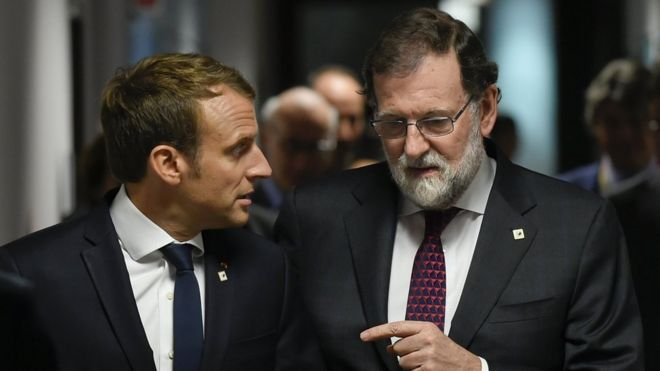 French President Emmanuel Macron (L) talks with Spanish Prime minister Mariano Rajoy (R) prior to their meeting, during the EU leaders summit on the first day of the European Council in Brussels