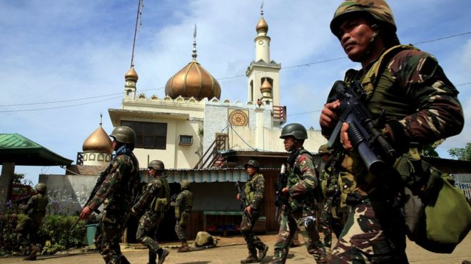 Government troops walk past a mosque before their assault with insurgents from the so-called Maute group, who have taken over large parts of Marawi City, southern Philippines 25 May 2017
