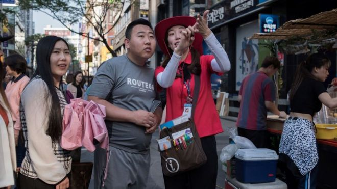 South Korean tour guide giving directions to Chinese tourists