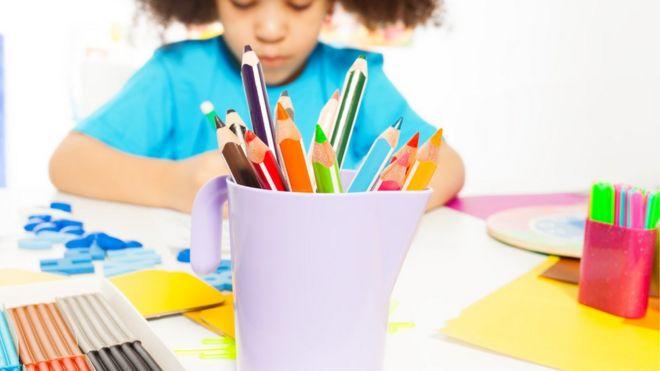 Criança desenhando com lápis coloridos em escola