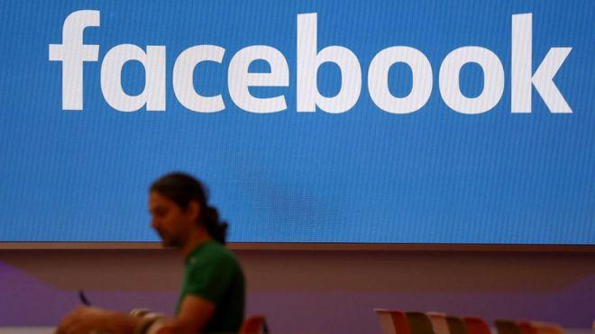 Homem diante de logo do Facebook