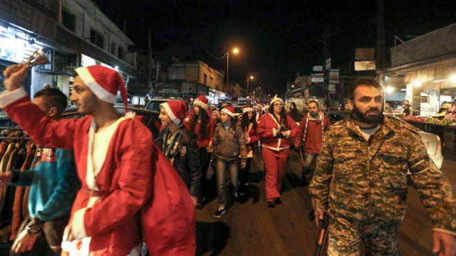 Người dân Syrian trong trang phục Giáng sinh xuống đường ở thủ đô Damascus đêm Noel 24/12/2017, được hộ tống bởi lực lượng cảnh sát Syria.