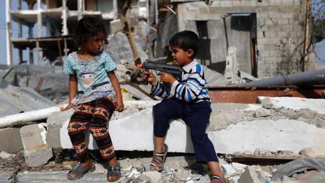 Niño apunta con pistola de juguete a niña
