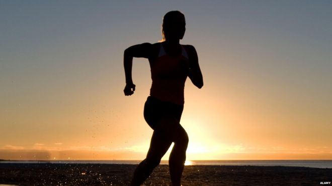 Woman silhouette running against sunset