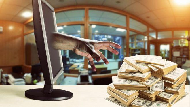 Mano saliendo de la pantalla de una computadora para agarrar un fajo de billetes.