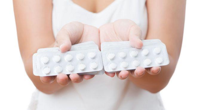 Mujer con pastillas de paracetamol