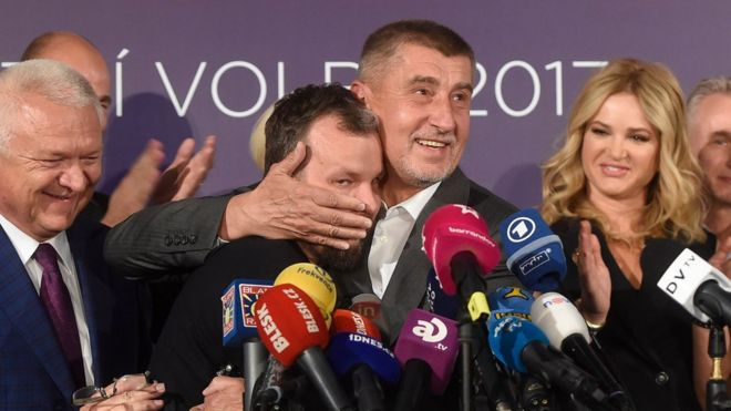 Czech billionaire Andrej Babis (C,R), chairman of the ANO movement (YES) kisses Marek Prchal, PR manager of ANO for social media at ANO headquarter after Czech elections on October 21, 2017 in Prague.
