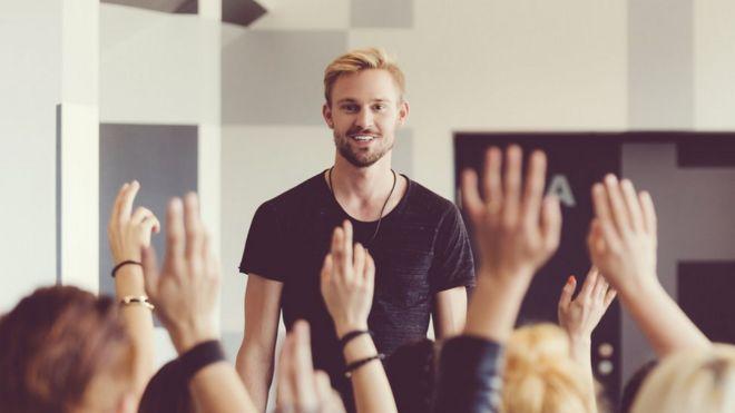 gente levantando la mano en una presentación