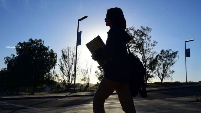 aluna andando com mochila e caderno