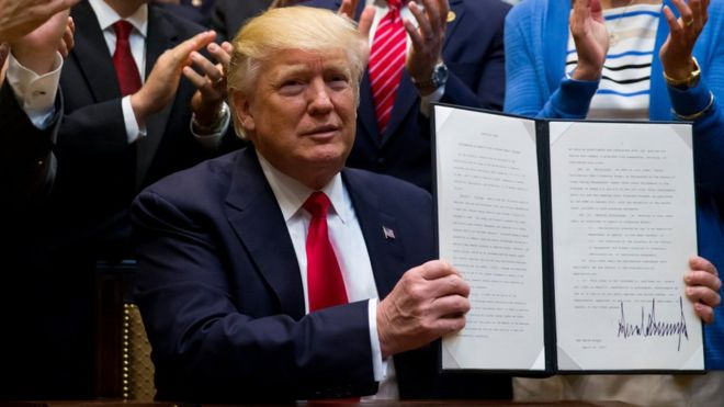 Donald Trump holds up an executive order while people behind him clap