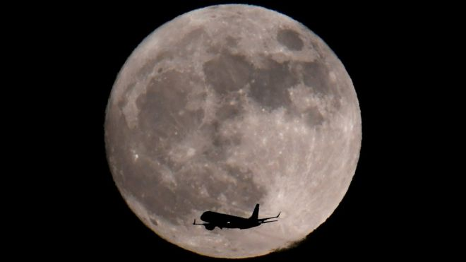 Un avión captado delante de la luna