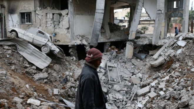 A man is seen near rubble of damaged buildings after an airstrike on the Eastern Ghouta town of Misraba, Syria, January 4, 2018.