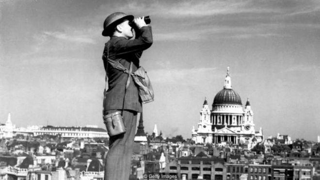 Một người lính phòng không theo dõi bầu trời London trong thời Đức ném bom, khi đó tòa thánh St Paul vượt cao trên hết mọi công trình ở thành phố.