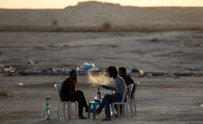 لاجئون من إريتريا يدخنون الشيشة