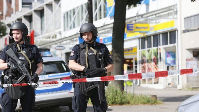 Police cordon off the area around a supermarket in the northern German city of Hamburg, where a man killed one person - 28 July 2017