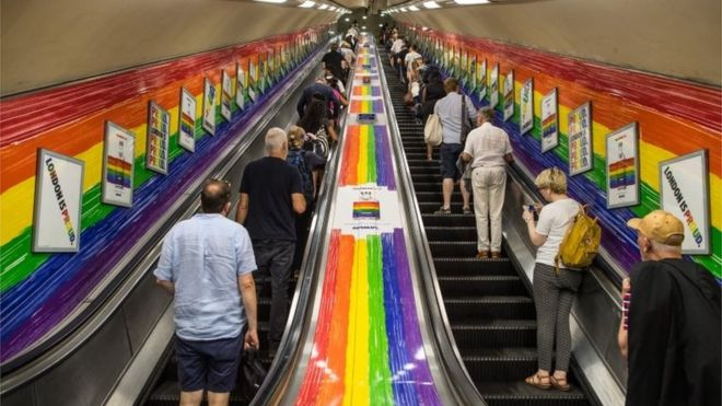 People ride a tube escalator decorated with the Pride flag colours