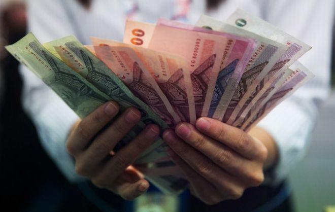 A money exchange bank teller counts Thai baht in Bangkok, Thailand.