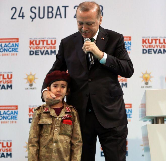 Turkish President Recep Tayyip Erdogan speaks alongside a girl dressed as a Turkish soldier
